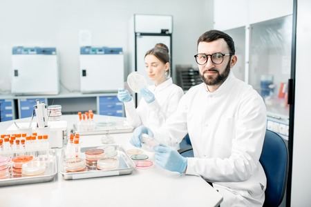 Portrait of a man in medical uniform during the bacteriological tests sitting with assistant in the modern laboratory