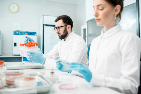 現代の実験室に座っている細菌学的検査を作る制服の薬のカップル