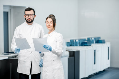 Portrait of a couple of medics working with paper documets standing in the laboratory with analyzer machine on the background