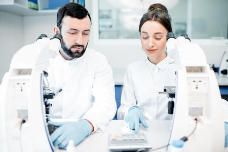 Couple of medics in uniform working with microscope making analysis at the laboratory office Stock Photo