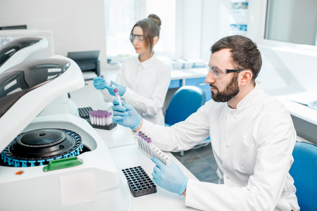Laboratory assistants making analysis with test tubes and analyzer machines sitting at the modern laboratory