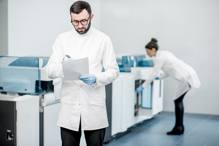 Man with woman technicians expertising analyzer machine in the laboratory