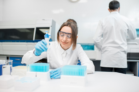 Young female laboratory assistant in uniform and protective glasses working with test tubes in the medical laboratory