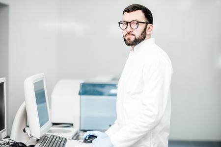 Male technician working with analyzer machine at the laboratiry