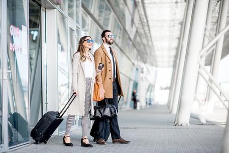 Biznesowa para w płaszczach wychodzi z lotniska z bagażem podczas podróży służbowej