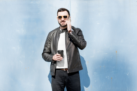Portrait of stylish man in leather jacket talking with phone on the blue wall background outdoors
