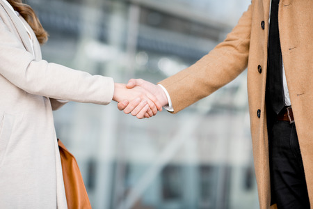 Handshake of a business partners on the modern building background