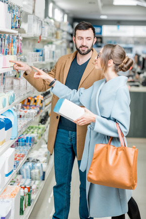 Young couple dressed in coats choosing medicine standing with box in the pharmacy store Reklamní fotografie