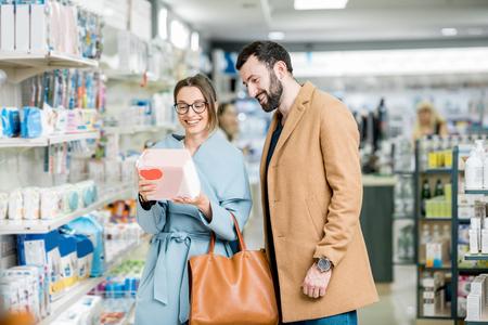 Junges Paar, das Windeln für Baby wählt, das im Apothekenladen steht