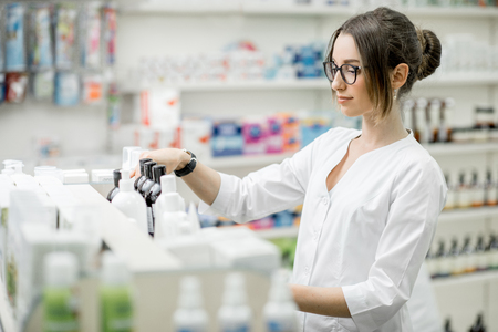 Young woman pharmacist supervising medicaments in the pharmacy store