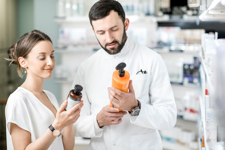Pharmacist helping young woman client to choose cosmetics at the pharmacy store Stock Photo