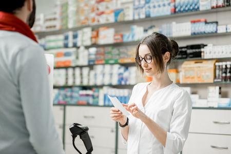 Pharmacist looking on the prescription selling medications at the paydesk of the pharmacy store