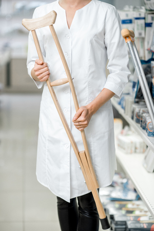 Doctor holding crutches at the pharmacy store, close-up view with no face