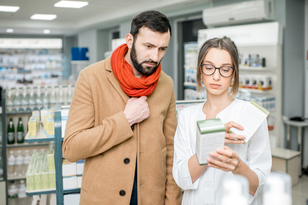 Young woman pharmacist choosing medicine with male client dressed in coat and scarf in the pharmacy store Stock Photo