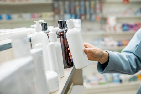 Woman taking a bottle with cosmetics from the shelf of the pharmacy supermarket, close-up view on the bottle with blank label