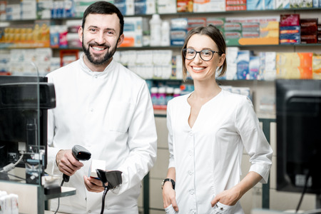Retrato de dos farmacéuticos que trabajan en la mesa de pago vendiendo medicamentos en la tienda de farmacia