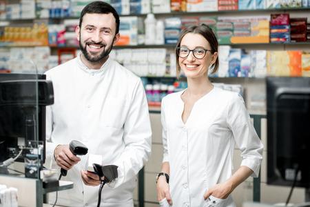 Ritratto di due farmacisti che lavorano presso la cassa che vende farmaci in farmacia