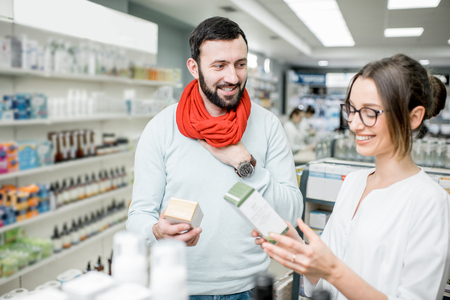 Pharmacist helping to choose medications for the man suffering from cold standing in the pharmacy supermarket