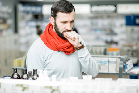 Portrait of a man in red scarf suffering from cold looking for some medicaments in the pharmacy supermarket