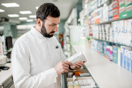 Handsome pharmacist searching for a medication in the storage of the pharmacy store
