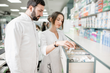 Man and woman pharmacists searching for a medication in the storage of the pharmacy store