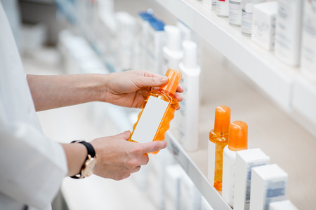 Taking sunscreen lotion from the shelves of the pharmacy store, close-up view
