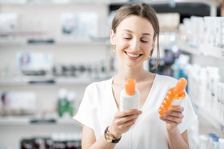 Cliente joven elegir loción de protección solar en la tienda de farmacia Foto de archivo