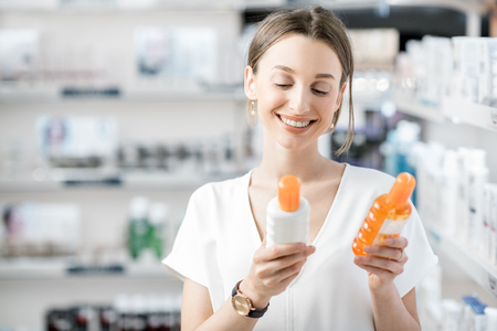 Young woman customer choosing sunscreen lotion at the pharmacy store Imagens