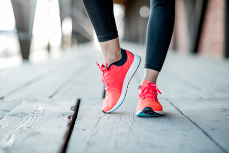 Sports woman in running shoes standing on the wooden floor, close-up view focused on the sneakers Archivio Fotografico