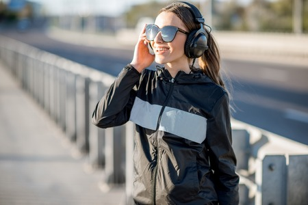 Portrait of a young woman in black sportswear with headphones standing on the bridge during the sunny morning Stock fotó