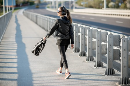 Young sports woman walking with bag after the sport training on the bridge in the city Stock fotó
