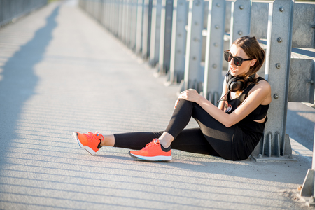 Sports woman having knee trauma sitting outdoors after the morning run Stock Photo