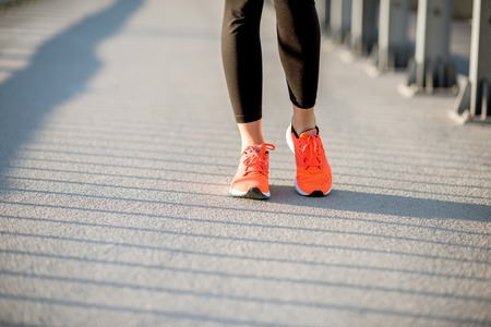 Woman in orange running shoes standing outdoors, close-up view focused on the sneakers Stock Photo