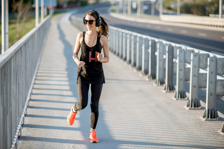 Woman in black sportswear running on the road bridge during the morning exercise Stock fotó