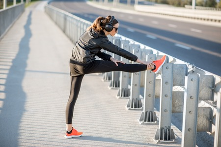 Woman in black sportswear stretching on the bridge during the morning exercise