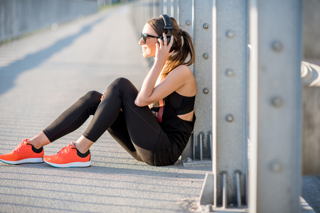 Young sports woman sitting on the road bridge having a rest after morning exercise
