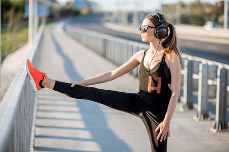 Young female runner in black sportswear stretching on the bridge during the morning exercise Stock fotó