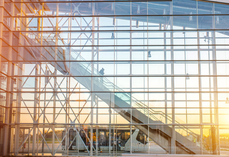 View on the modern transparent facade with escalator at the airport