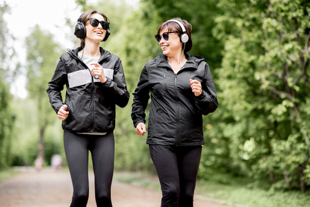 Young and elder woman in black sportswear running in the park during the morning exercise