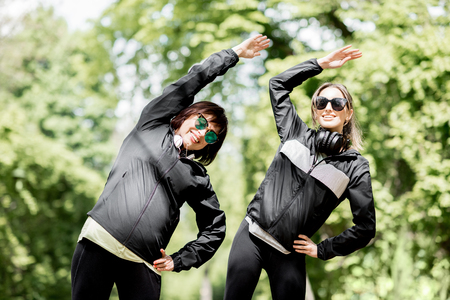 Young and elder woman in black sportswear stretching in the park during the morning exesrcise