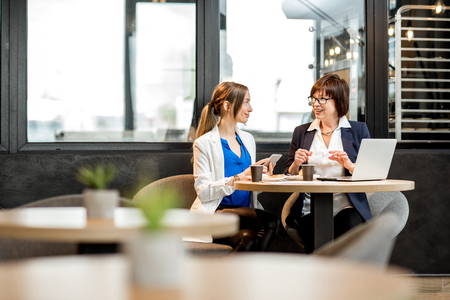 Senior business woman with young partner dressed in suits working with laptop in the modern cafe Stock Photo