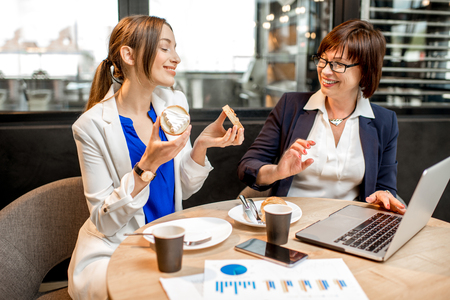 Senior business woman with young partner dressed in suits having a coffee time with sweet desserts in the modern cafe
