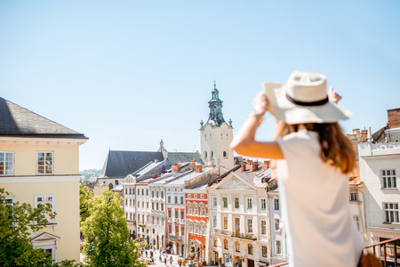 Young woman tourist enjoying great view on the old town in Lviv city during the sunny weather in Ukraine. Image focused on the background Stock Photo