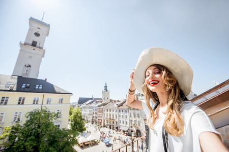 Selfie portrait of a young and happy woman tourist standing on the beautiful old town view background in Lviv city, Ukraine 版權商用圖片
