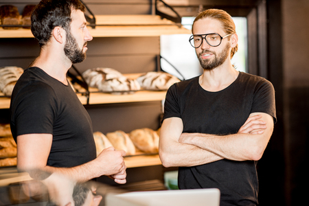 Two businessmen or salesmen in black t-shirts working with laptop at the bakery shop counter Stock Photo