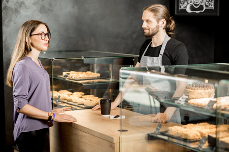 Handsome barista with young woman customer standing at the counter of the pastry store with sweet delicacies