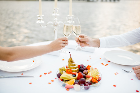 Couple clinking wine glasses during romantic dinner on the riverside. Close-up view Banco de Imagens
