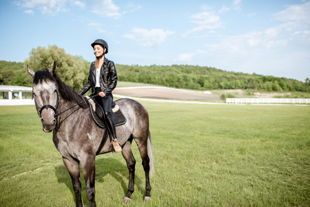 Woman in leather jacket with protective helmet riding a horse on the green meadow Banque d'images - 101476342