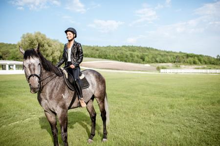 Frau in der Lederjacke mit dem Schutzhelm, der ein Pferd auf der grünen Wiese reitet