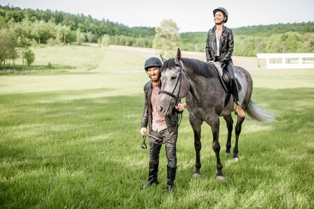 Man leading a horse with woman rider on the beautiful green meadow during the sunny weather Reklamní fotografie